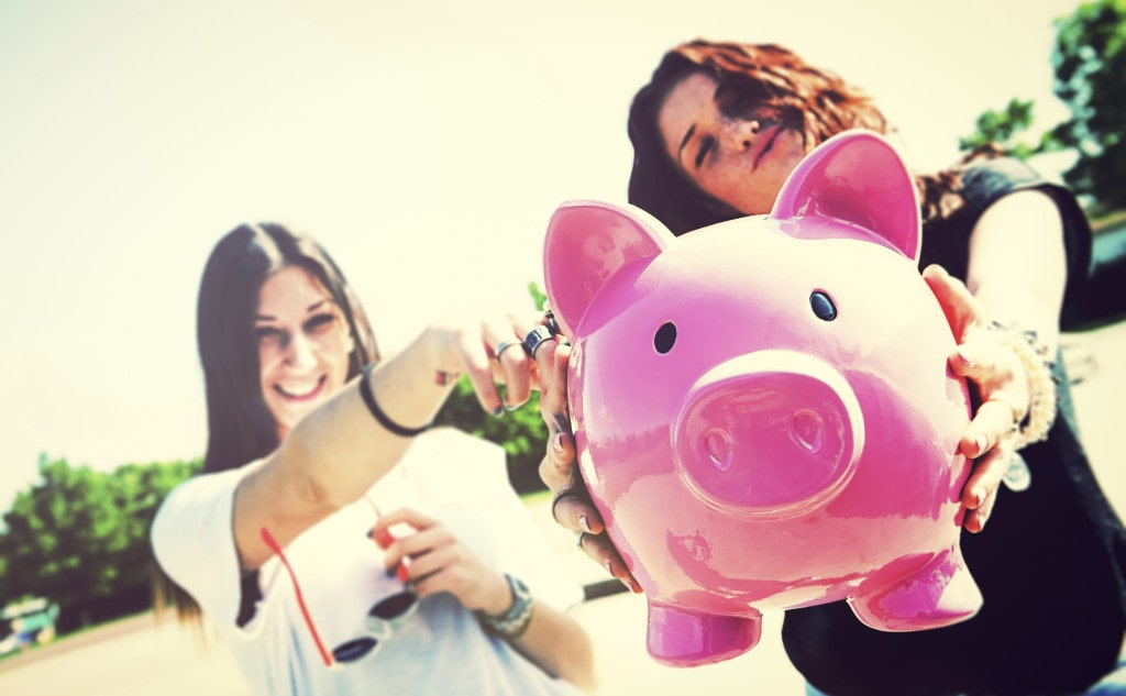 Two young funny woman holding piggy bank talking about Cost of LASIK