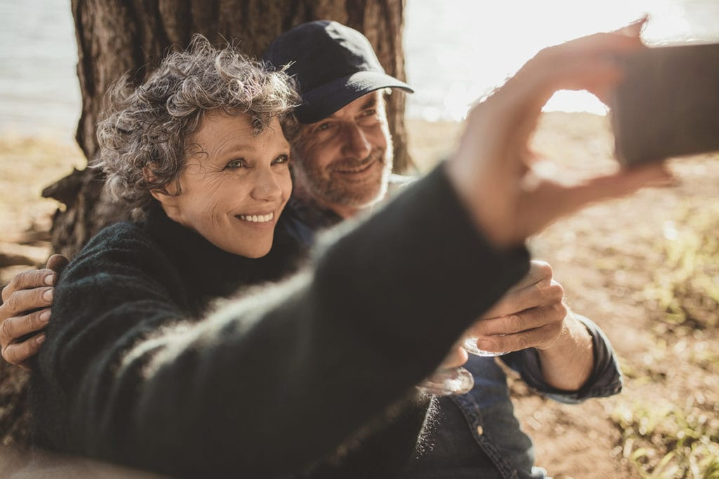 Happy senior couple discussing cataracts and taking their self portrait with their cell phone on camping day. Man and woman sitting together outdoors at campsite and taking selfie.