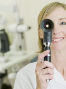 eye doctor examining patient with opthalmoscope